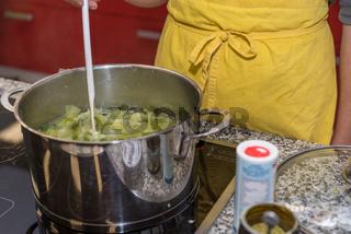Koch rührt mit Kochlöffel im Kochtopf um - Nahaufnahme