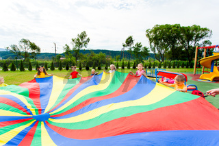rainbow parachute waived by kids in the summer outdoors