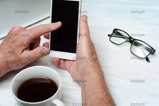 Top view of old man hand holding a cup of coffee and smartphone