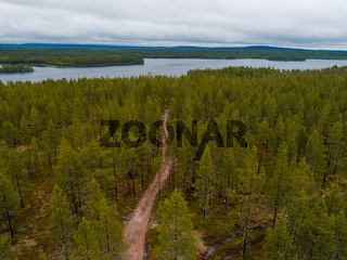 Finland, a gravel road through forest to the lake in Lapland