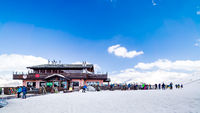 Skiers, snowboarders relaxing near mountain hut, Alps, Livigno, Italy