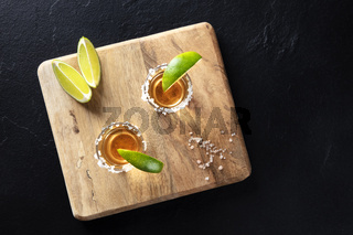 Golden tequila shots with salt and lime slices, shot from above on a black background with copy space