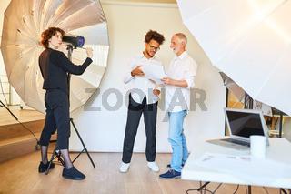Fotograf mit Art Director und Fotoassistentin