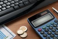 A calculator on wooden table with a pen and some euro coins in front of a black computer keyboard