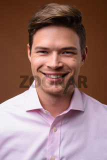 Studio shot of young handsome businessman with pink shirt