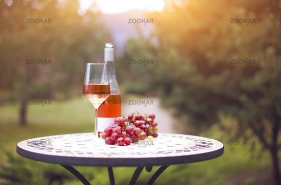 One glass and bottle of rose wine in autumn vineyard on marble table
