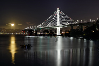 Full moon rising over the new eastern span of the San Francisco-Oakland Bay Bridge at night.