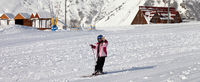 Little skier at ski resort in sun winter day