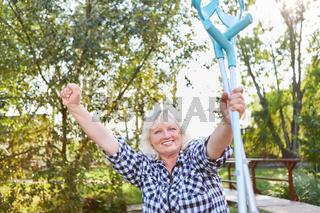 Jubelnde Senior Frau mit Krücken in der Reha