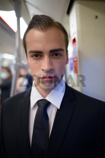 Face of young businessman looking at camera in train