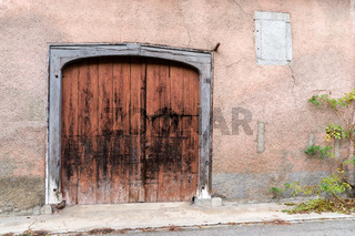 large vintage wooden garage door or gate in a historic pink house front with a green vine plant on t