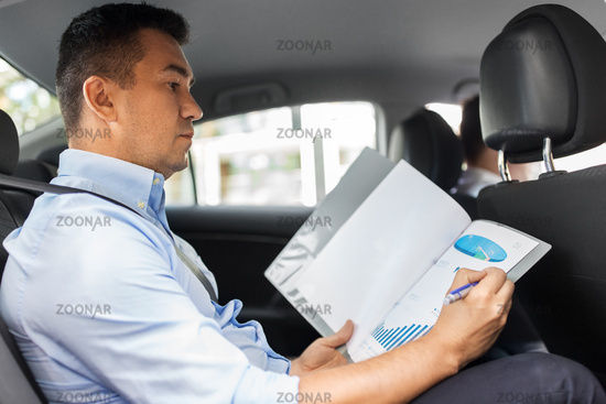 businessman with charts in folder working in car
