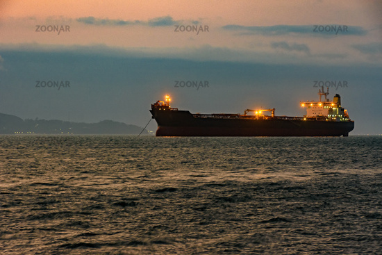 Big cargo ship anchored in the waters of Ilhabela Island at sunset