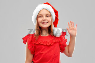 smiling girl in snata helper hat waving hand