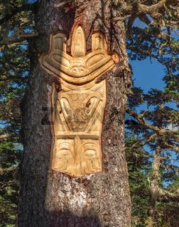 September 14, 2018 - Juneau, Alaska: Tlingit carving on live tree trunk, Mount Roberts Tramway.