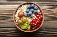Flat lay view at oats in clay bowl with berries on wooden table