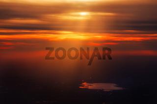 Deep Orange Red Sunset Coming Through Clouds on Dark Landscape Pond Water Sunrays