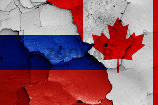 flags of Russia and Canada painted on cracked wall