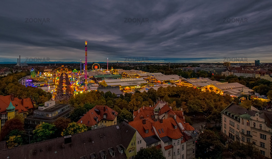 The Oktoberfest / Wiesn in Munich in total view at the evening with colorful lights from above.