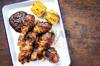 Traditional barbecue chicken drumsticks with corm and hot chili sauce as top view in a white fryer with copy space right