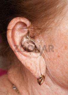 Hearing aid device in senior woman ear - closeup photo