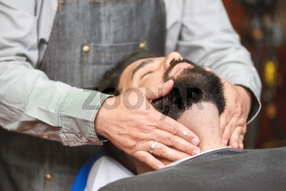 Hair stylist applying after shaving lotion at barber shop.