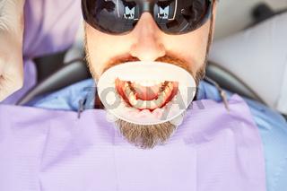 Patient mit weit offenem Mund beim Zahnarzt