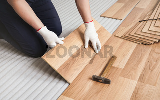 Man installing laminated floor, detail on wooden tile being fitted, over white foam base layer