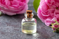 A bottle of rose essential oil with cabbage roses