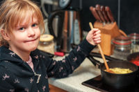 Child in the kitchen at the stove while cooking
