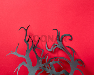 Halloween composition of paper handcraft branches of trees on a red background with space for text. Postcard. Flat lay