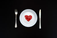 On a white plate from pomegranate seeds composite heart shape. Knife and fork next to the plate.