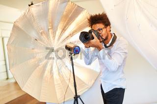 Kreativer junger Fotograf mit digitaler Kamera