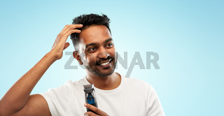 smiling indian man with trimmer touching his hair