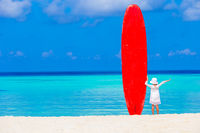 Adorable little girl with big surfboard during tropical vacation