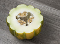 Half of ripe fresh melon with seeds isolated on wooden background. Sweet tropical fruit.