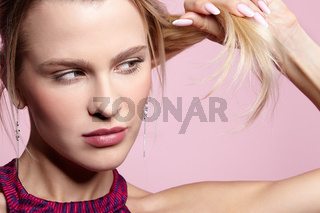 Female with blonde hair ponytail looking on splitting hair ends