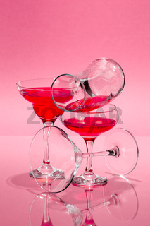 The composition of glasses of various shapes with a red liquid on a light pink background.