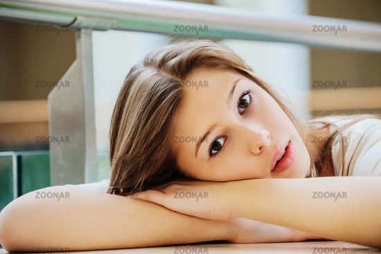 Young beautiful woman with long hair sits at table