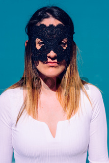 Vertical portrait of attractive young woman with black mask on her face and white shirt, serious gesture, to keep her privacy.