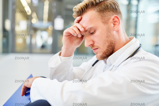 Junger Arzt sitzt erschöpft im Krankenhaus