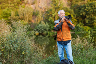 Älterer Fotograf als Landschaftsfotograf in der Natur