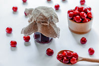 Red ripe cherries with jam jar and wooden spoon on white background. Flat lay. Food concept.