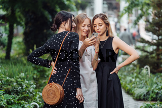 Three girls look at the photo