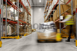 worker carrying loader with goods at warehouse