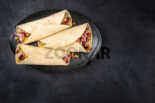 Burrito sandwich wraps, top shot on a black background. Tortillas stuffed with ground beef meat, rice, beans, onions, and chili peppers, with copy space