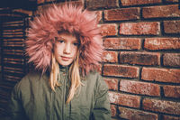 Young girl wearing fur jacket standing in front of brick wall and looking at camera