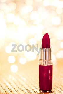 Dark red lipstick on golden Christmas, New Years and Valentines Day holiday glitter background, make-up and cosmetics product for luxury beauty brand