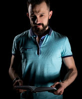 Studio photo of bearded man with book in his hands
