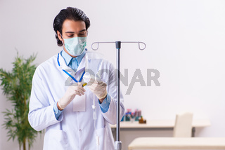 Young male doctor in blood transfusion concept